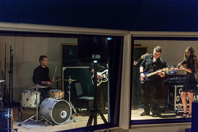 Students in the recording studio playing instruments