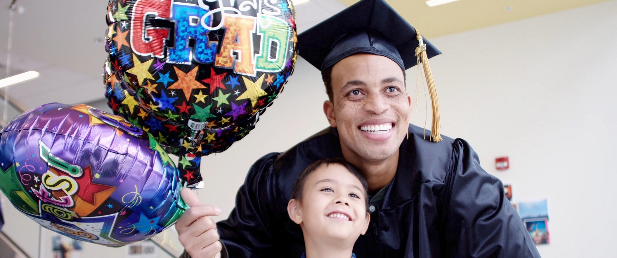 dad and son with grad baloons