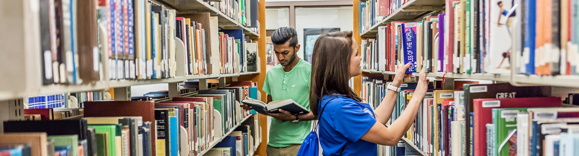 Two Students between two library shelves browsing books.